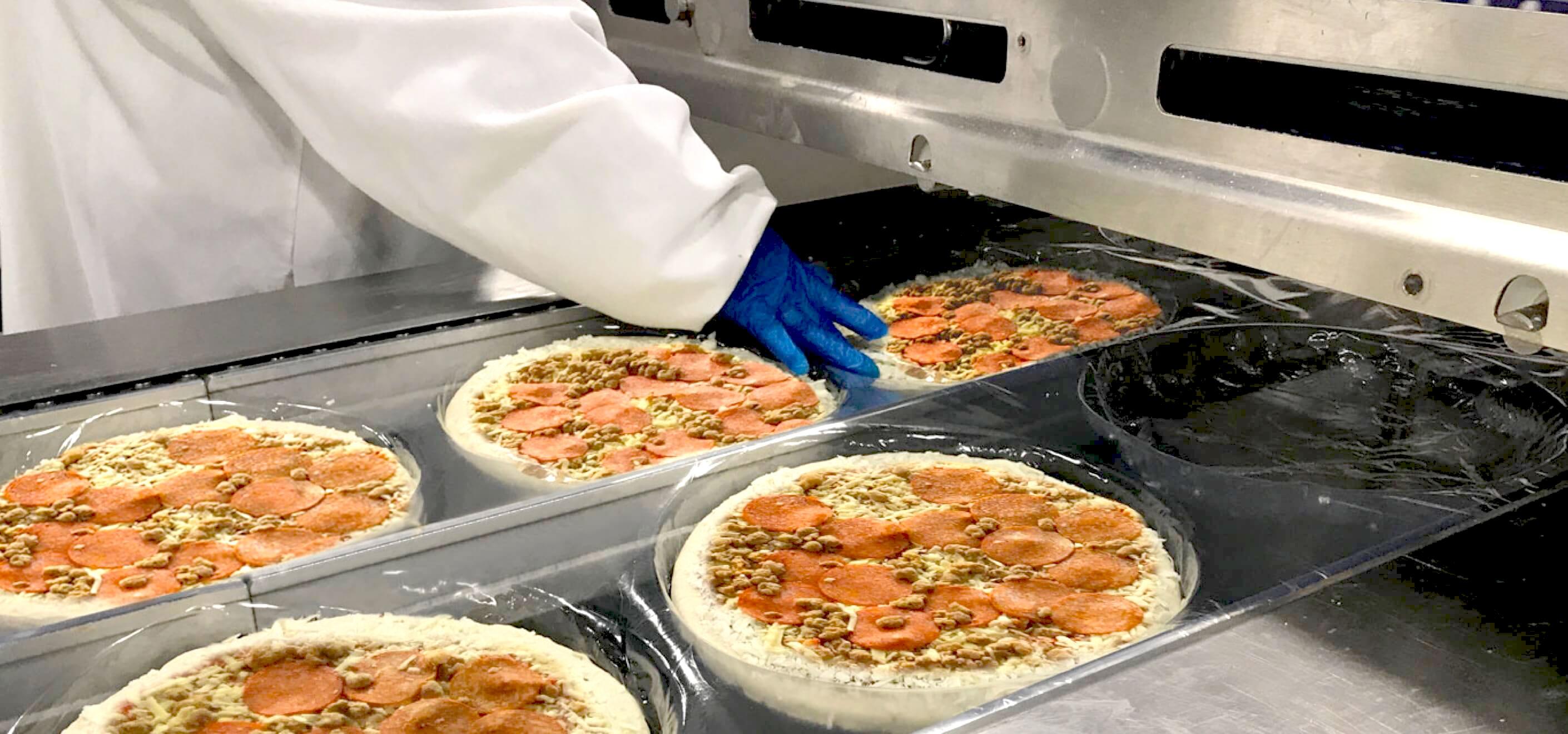 Pizza getting vacuum sealed.