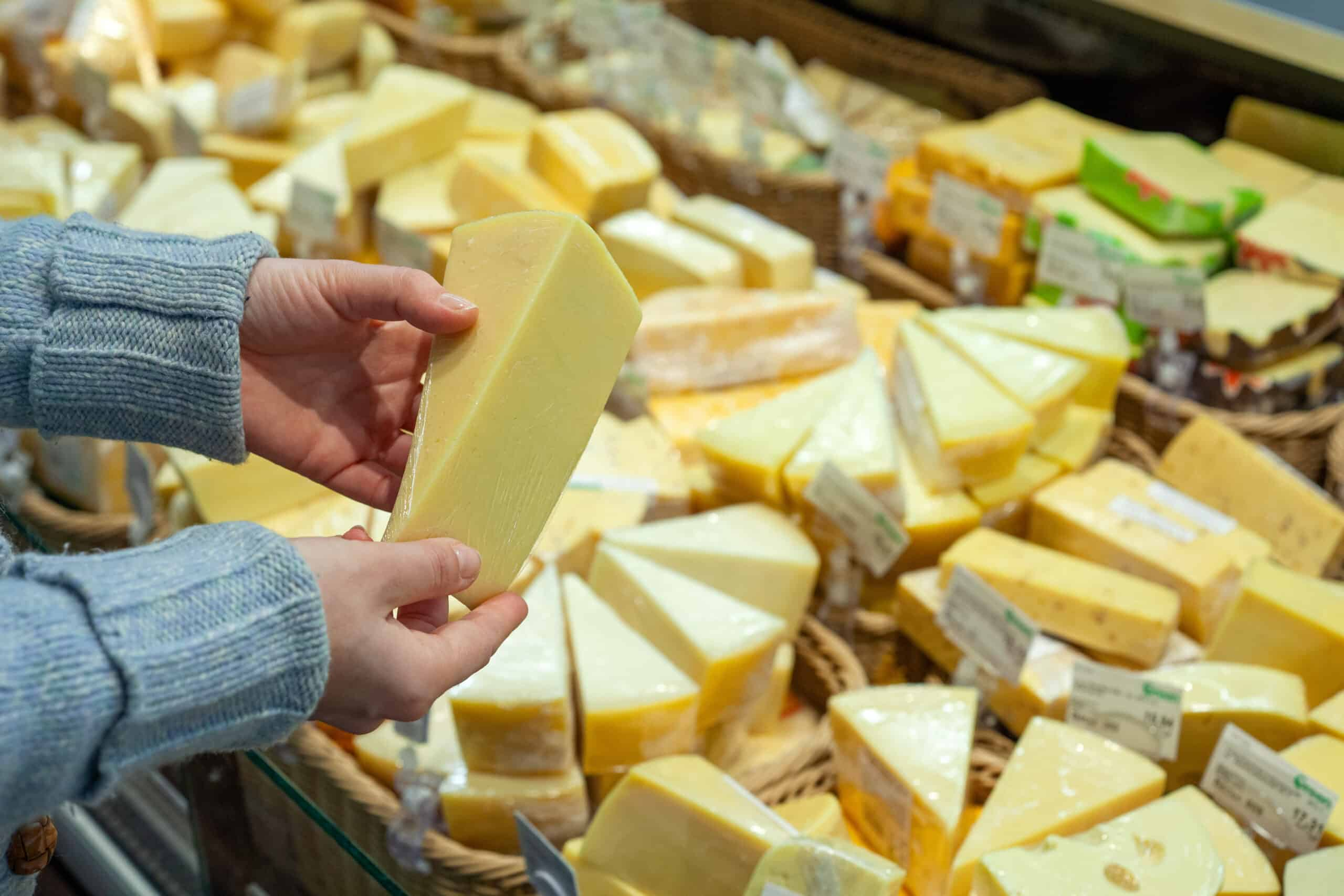 person holding packaged cheese